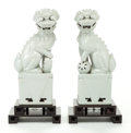 Asian:Chinese, A PAIR OF WHITE PORCELAIN FOO DOGS ON HARDWOOD STANDS. 20thcentury. 16-1/2 inches high (41.9 cm) (without stands). ... (Total:2 Items)