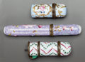 Decorative Arts, Continental:Other , TWO ENAMELED METAL CASED PERFUME VILES AND AN ENAMELED METAL NEEDLECASE. 19th century. 4-1/2 inches long (11.4 cm) (needle ... (Total:3 Items)