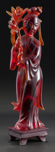 Asian, AN AMBER FIGURE OF A GUANYIN. 20th century. 8-3/4 inches high (22.2cm) (with base). ...