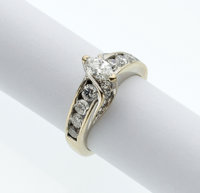 The ring features a marquise-cut diamond weighing approximately 0.30 carat, enhanced by full-cut diamonds weighing a tot...