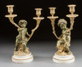 Decorative Arts, French:Lamps & Lighting, A PAIR OF FRENCH GILT AND PATINATED BRONZE FIGURAL TWO-LIGHTCANDELABRA ON MARBLE SOCLES IN THE MANNER OF CLODION. Early 20t...(Total: 2 Items)