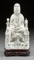 Asian:Chinese, A CHINESE BLANC DE CHINE FIGURE OF A SEATED GUANYIN WITH TWOGUARDIANS ON A CARVED WOOD BASE . 19th century. 9 x 5-3/4 x 2-1...