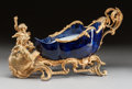 Ceramics & Porcelain, A FRENCH ROCOCO-STYLE COBALT GLAZED PORCELAIN AND GILT BRONZE MOUNTED FIGURAL CHARIOT-FORM CENTERPIECE. 19th century. 11 inc...