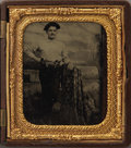 Photography:Tintypes, HAND-TINTED 1/6th PLATE TINTYPE OF COWBOY. A young cowboy withpistols in his belt poses before a studio backdrop of an outd...(Total: 1 Item)