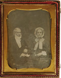 Photography:Daguerreotypes, Cased 1/2 Plate Daguerreotype of an Elderly Couple. A charming studio portrait, circa 1850, showing a serious man and his pl...
