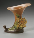 Ceramics & Porcelain, American:Modern  (1900 1949)  , AN AMERICAN ART POTTERY VASE. Roseville Pottery, designed 1943. Thecornucopia form vase in the 'Water Lily' pattern, depi...