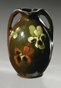 Ceramics & Porcelain, American:Modern  (1900 1949)  , AN AMERICAN POTTERY VASE. McCoy, early 20th century. The ovoid formwith applied handles decorated with pansies on the bro...