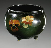 AN AMERICAN POTTERY VASE McCoy, c.1899-1911  The ovoid form on tripod, applied feet decorated with pansies on a dark gre...