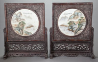 A PAIR OF CHINESE PAINTED PORCELAIN TABLE SCREENS IN CARVED WOOD FRAMES AND STANDS Marks: (chop marks) 30-1/4 x