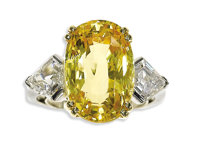 Yellow Sapphire, Diamond, Platinum, Gold Ring  The ring centers a cushion-shaped yellow sapphire measuring 16.11 x 10.75...