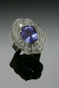 Jewelry, A Ladies 18K White Gold Fashion Ring Centered With Tanzanite Accented With Diamond Baguettes. The band weighing 10.8 gms m...