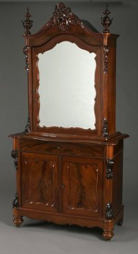 AN AMERICAN VICTORIAN GOTHIC STYLE TWO-PART CABINET Nineteenth Century  The carved, two-piece mahogany cabinet with mirr...