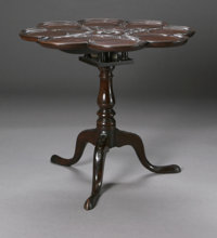 A GEORGIAN TILT TOP TABLE American, Late Nineteenth Century  The mahogany tilt-top table of lobed form, stylized carved...
