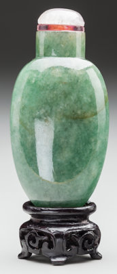 A CHINESE CARVED JADE SNUFF BOTTLE ON A CARVED MAHOGANY STAND 2-1/4 inches high (5.7 cm)  PROPERTY FROM THE