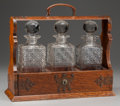 Decorative Arts, Continental, AN OAK AND COPPER TANTALUS DECANTER RACK WITH THREE FITTEDCUT-GLASS DECANTERS, early 20th century. 13 x 14-3/4 x 5-1/2inch... (Total: 4 Items)