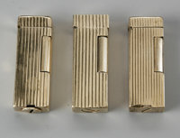 THREE 14K GOLD DUNHILL LIGHTERS Alfred Dunhill of London, Inc.  The three 14K gold (outer jacket) lighters, Dunhill logo...