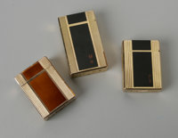 A GROUPING OF THREE FRENCH LIGHTERS St. Dupont, France  The group of three gold lighters with textured surfaces and enam...