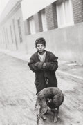 Photographs, Sergio Larrain (Chilean, b. 1931). Boy and Dog on Street, 1957. Gelatin silver, printed later. 13-1/2 x 9 inches (34.3 x...