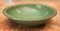 Asian, A Chinese Green Glazed Pottery Bowl with Incised Decoration. 14inches diameter (35.6 cm)...