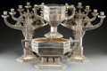 Decorative Arts, Continental, A Four-Piece Art Deco Silvered Metal Table Garniture, 20th century.19-5/8 inches high (49.8 cm) (tallest, menorah). ... (Total: 4Items)