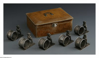 Six American Silver Napkin Rings and Case Mark of Wilbur Hansen, c.1900  The six matching figural rings depict a round r...