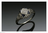 A White Gold, Diamond And Sapphire Ring  The Art Deco-style ring in 18k white gold with an open-work mount supporting fo...