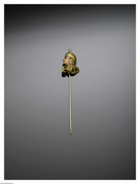 A GOLD AND ENAMEL STICK PIN  The 14K gold Egyptian Revival stick pin depicting a female head in profile, the face in ena...