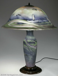 An American Reverse-Painted Glass Lamp Pairpoint Corporation, Early Twentieth Century  The wooden foot supports a slight...