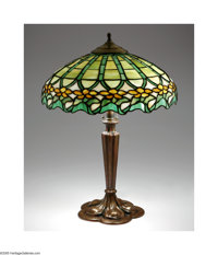 An American Stained Glass And Metal Lamp Attributed to Duffner and Kimberly, c.1915  The white metal lamp base with a fl...