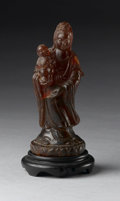 Asian:Chinese, CHINESE CARVED AMBERINE FIGURE. Chinese carved amberine figure of aguayin, holding a child in one arm. With wood stand. 6...