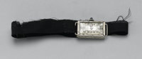 A LADY'S WRIST WATCH Hallmark  The wristwatch with black fabric band, rectangular case, metal dial with Arabic numerals...