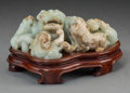Asian:Chinese, A Chinese Carved Celadon and Russet Jade Fu Lion Group with Stand.2-3/4 h x 6-1/8 w x 3-1/2 d inches (7.0 x 15.5 x 8.9 cm) ...
