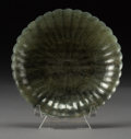 Asian:Chinese, A Chinese Spinach Jade Floral Form Plate, Qing Dynasty. 5 inchesdiameter (12.7 cm). ...