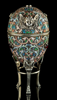 A Russian 3rd Artel Enameled and Garnet Cabochon-Mounted Silver Egg with Applied Cherub Heads on Married Stand, St. P