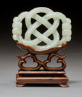 Carvings:Chinese, A Chinese Carved White Jade Endless Rope Knot Toggle on Hardwood Stand, Qing Dynasty. 2-1/8 x 2-7/8 inches (5.4 ...
