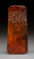 Carvings, A Japanese Brown Jade Pendant with Aboriginal Facial Design. 5-3/4 x 2-1/2 inches (14.6 x 6.4 cm). PROPERTY FROM A BEVERLY...