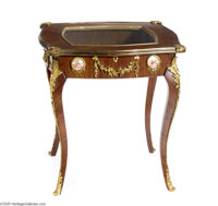 A MAHOGANY VITRINE TABLE Maker unknown, 20th century  In Louis XV style with metal mounts and round Sèvres-style...