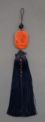 A Chinese Carved Coral Plaque with Indigo Knotted Silk Tassel, Qing Dynasty 17 x 2 inches (43.2 x 5.1 cm)
