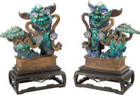 A Pair of Chinese Glazed Stoneware Foo Dogs on Carved Hardwood Stands 27 x 24 x 13 inches (68.6 x 61.0 x 33.0 cm)