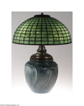 Lighting:Lamps, Tiffany: AN ARTS AND CRAFTS POTTERY LAMP WITH LEADED GLASS SHADE (Tiffany) . Tiffany, c.1900. The shade with heavy mottlin...
