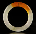 Carvings, A Chinese Jadeite Bangle with Russet Splash, 20th century. 3-1/4 x 0-1/2 inches (8.3 x 1.3 cm). ...