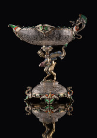 A Hermann Ratzersdorfer Gem-Set, Partial Gilt, and Enameled Silver-Mounted and Engraved Rock Crystal Figural Tazza, V