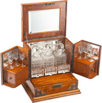 A Continental Mahogany Cave à Liqueur with Three Cut-Glass Decanters, Six Cordial Glasses, and Three Metal Trays...