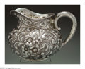 Silver & Vertu:Hollowware, AN AMERICAN SILVER REPOUSSE WATER PITCHER. Mark of Dominick & Haff, New York, c.1887. The baluster body with repousse flow...
