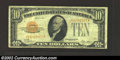 Small Size:Gold Certificates, 1928 $10 Gold Certificate, Fr-2400, VF. There are three heavy ...