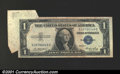 Error Notes:Attached Tabs, 1935E $1 Silver Certificate, Fr-1614, VF. A fold before cutting...