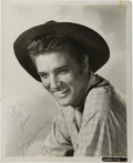 "Music Memorabilia:Autographs and Signed Items, Elvis Presley Signed Photo. A b&w 8"" x 10"" photo of Elvis inhis late 1950s era, in cowboy hat and rustic shirt, leaning int...(Total: 1 Item)"
