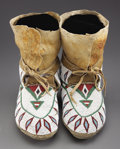 American Indian Art:Beadwork and Quillwork, A PAIR OF PLAINS CREE BEADED HIDE MOCCASINS. c. 1910... (Total: 2Items)