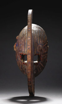Bobo (Burkina Faso) Mask with Crescent shape Wood, pigment, abrus seeds, fiber Height: 15 inches Width: 5 ¾ inche...