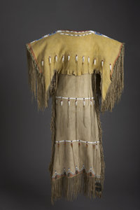 A SOUTHERN CHEYENNE GIRL'S BEADED AND FRINGED HIDE DRESS c. 1890